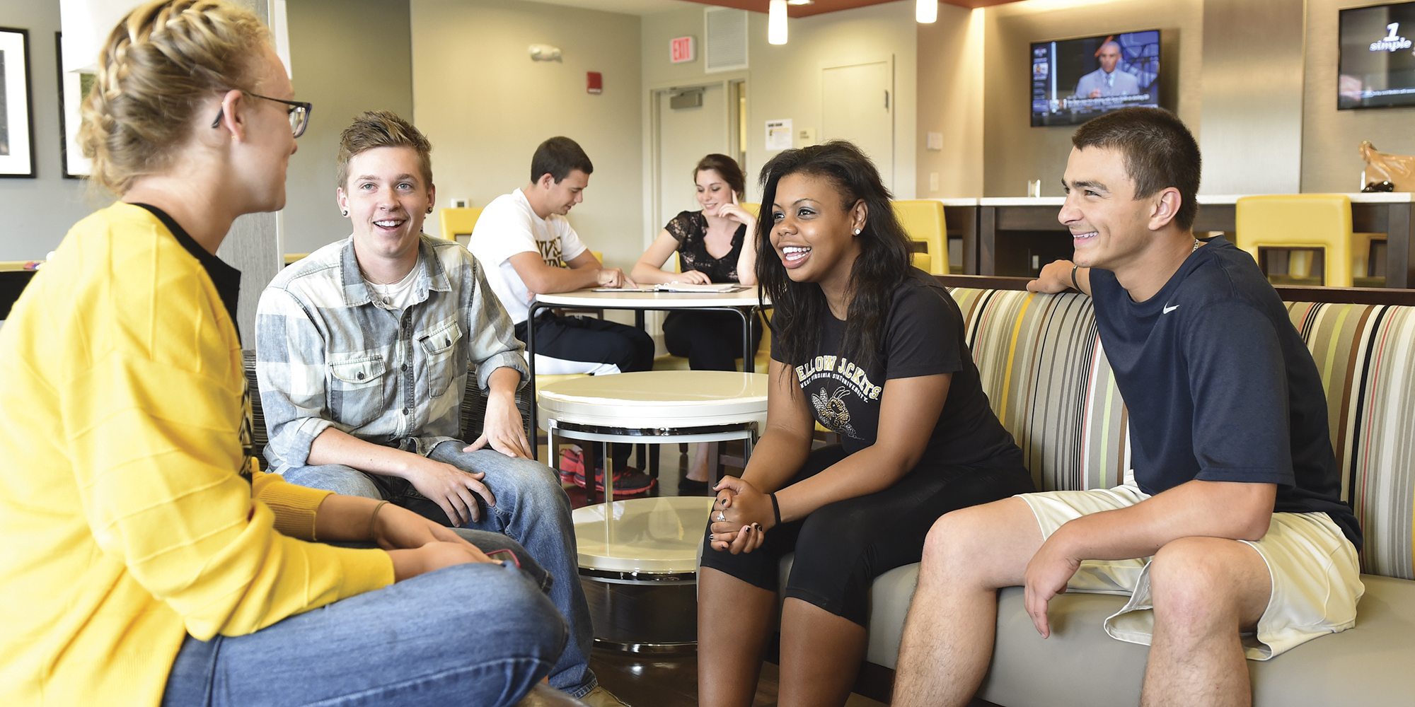 Students laughing, smiling in the cafe.