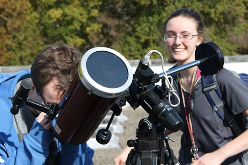 space club participants peer through a telescope